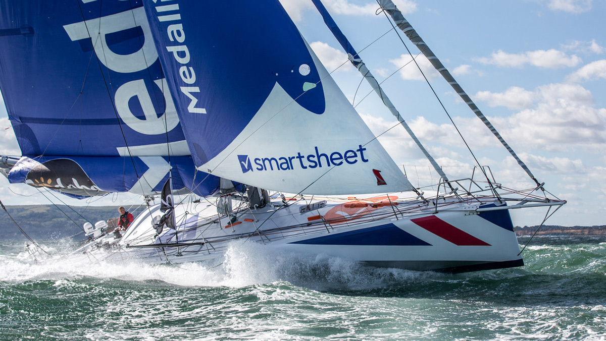 The Smartsheet logo appears on the sail of the Medallia, Pip Hare's competitive sail boat