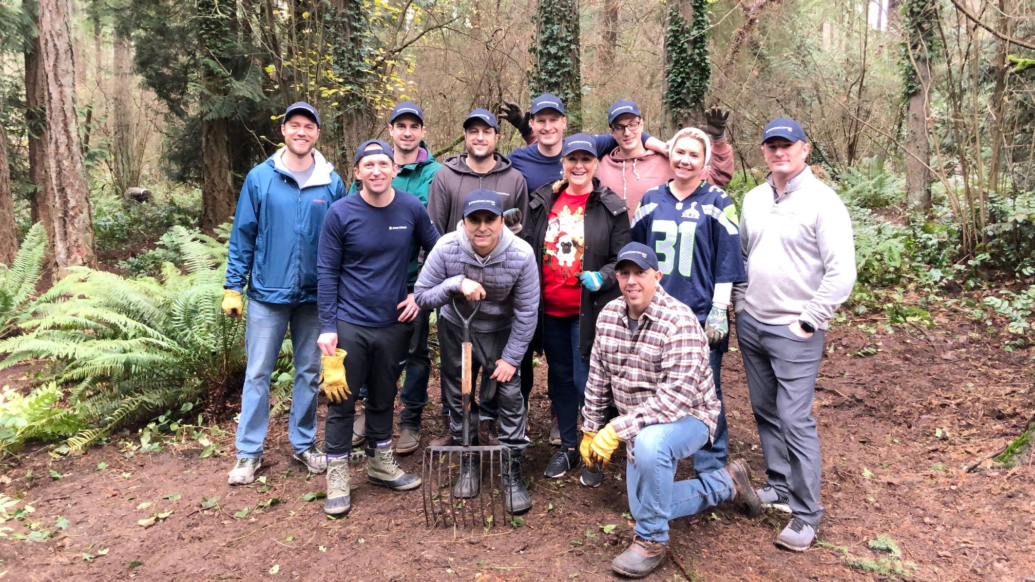 Smartsheet employees pose for a group photos amidst ferns and a wooded forest area.
